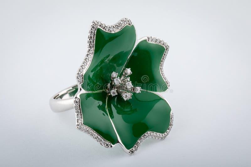 Anello a forma di fiore d'argento dalla pietra verde e diamanti in mezzo al fiore, isolato su fondo bianco immagine stock libera da diritti