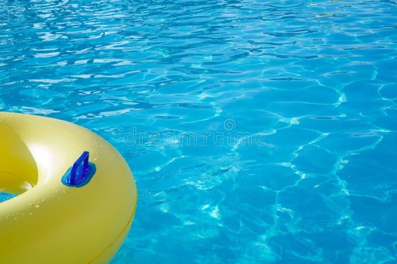 Anello giallo di nuotata in una piscina con acqua increspata, backgrou immagine stock libera da diritti