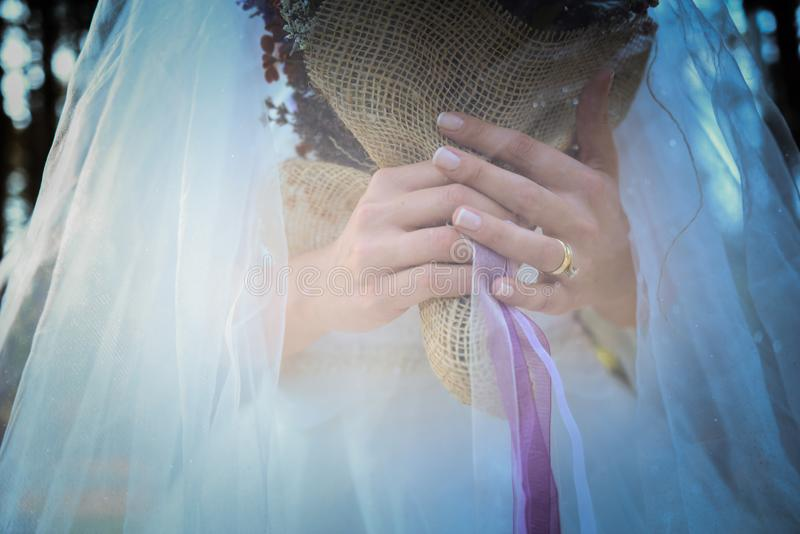 Anello nuziale di diamante e di velo della sposa sulla sua fine dell'anulare sulla vista fotografie stock