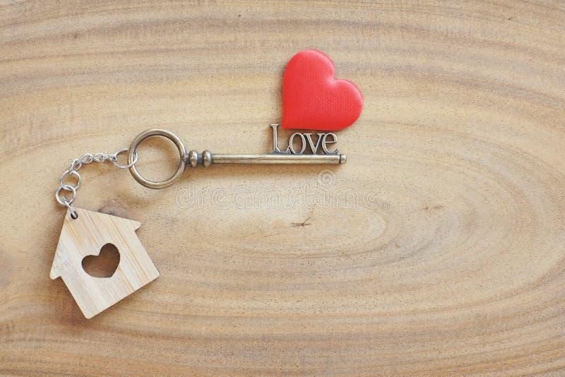 Anello portachiavi della Camera e chiave di forma di amore sulla tavola di legno d'annata Decorato con mini cuore come regalo dol immagini stock libere da diritti