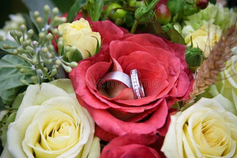Anello rosso di cerimonia nuziale e del fiore fotografia stock