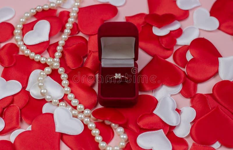 Anello in scatola rossa e perle su un fondo dei cuori di rosso e di bianco Fede nuziale nella scatola fotografie stock