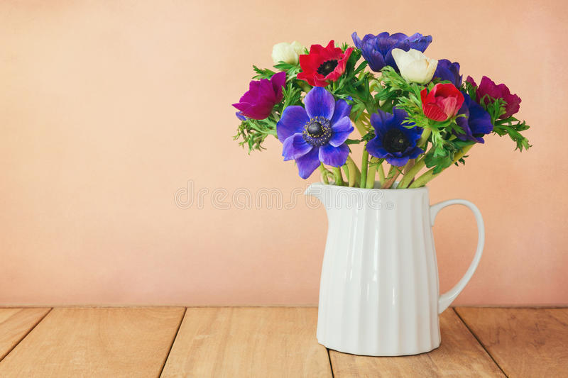 Anemone flowers in white vase on wooden table. Anemone flowers in white vase royalty free stock photos