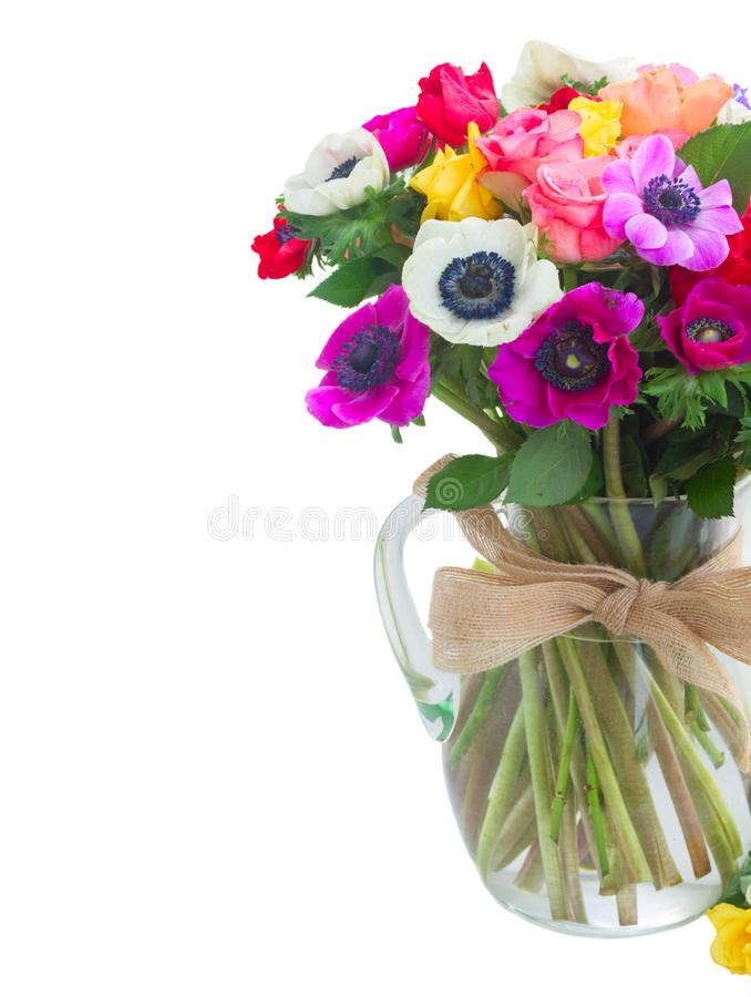 Anemones on white. Fresh Anemones and roses flowers bouqet in glass vase close up isolated on white background stock photography