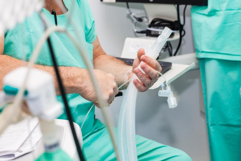 Anesthesiologist doctor getting ready to give anesthesia to the patient in the surgery room stock image