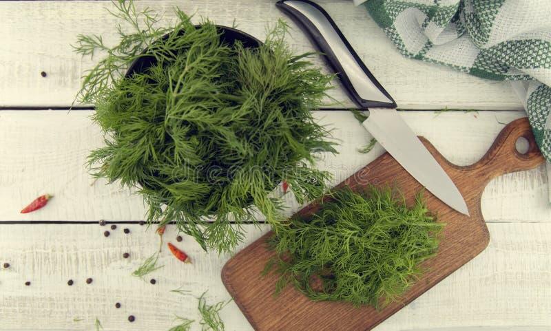Aneth organique frais sur une planche à découper et un groupe d'aneth sur le C.A. photo stock