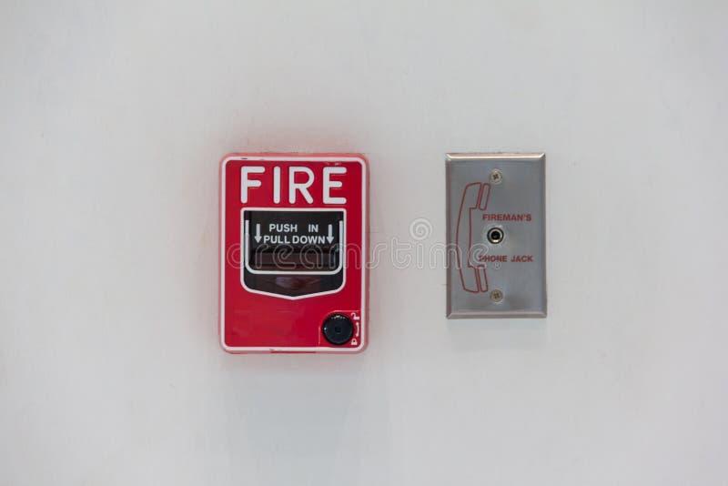 Anexo vermelho do interruptor do alarme de incêndio com parede branca imagem de stock royalty free