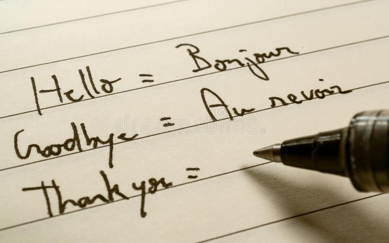 Anfänger des Anfängers französische Sprach, derwörter auf Französisch für Hausarbeit auf ein Notizbuch schreibt lizenzfreie stockfotos