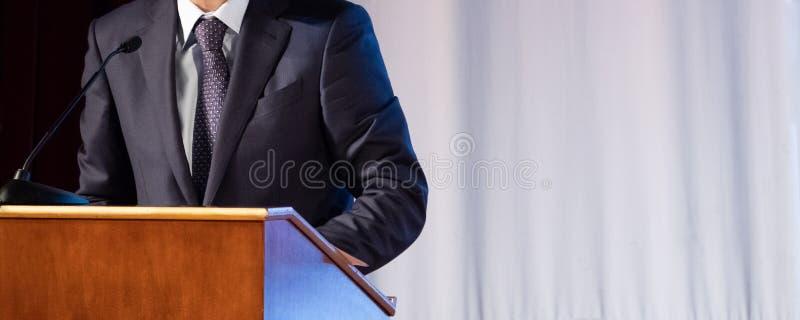 Anförande av en abstrakt man i en dräkt på etapp på ställningen för kapaciteter Tribun eller cathedra för högtalarerepresentanten arkivfoto