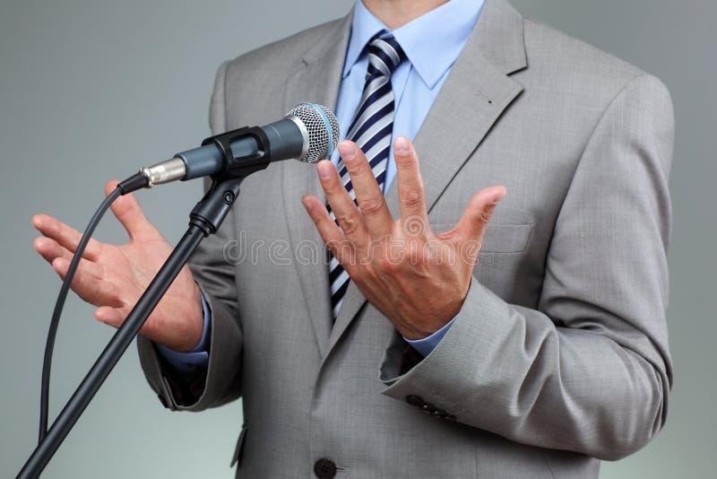 Anförande med mikrofon- och handgest royaltyfria foton
