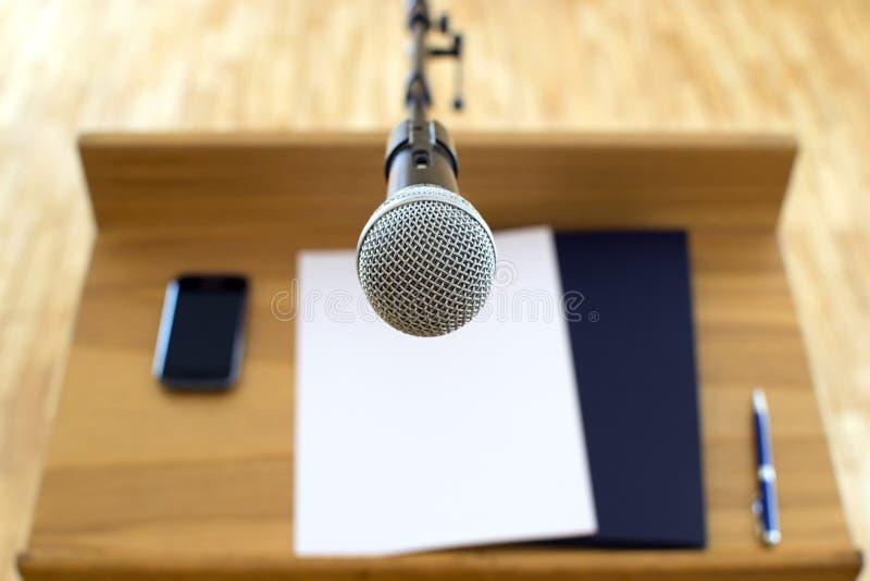 Anförandepodium och mikrofon framme av högtalaren royaltyfria foton