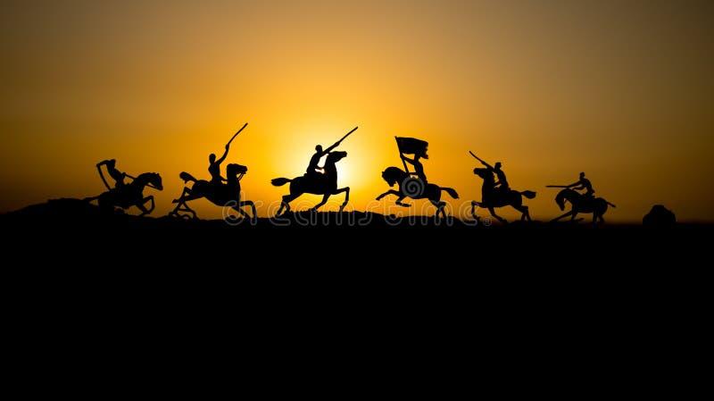 Anfalla plats oavkortat kugghjul för soldater Ryttare på hästen som är klar att slåss, och soldater på en mörk dimmig tonad solne royaltyfri fotografi