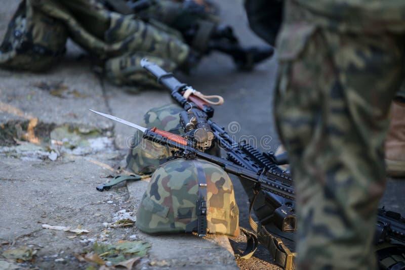 Anfallgevär, arméhjälmar med kameror och andra arméobjekt arkivbild