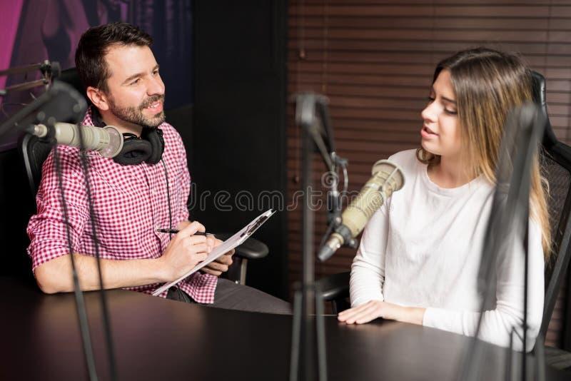 Anfitrião masculino que entrevista um convidado para o podcast foto de stock royalty free