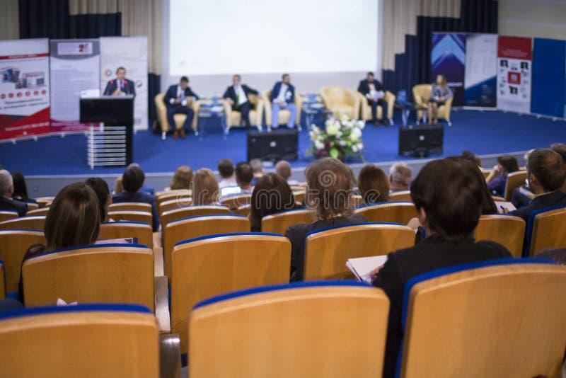 Anfitrião masculino que fala na fase durante a conferência de negócio no grande congresso Salão imagem de stock
