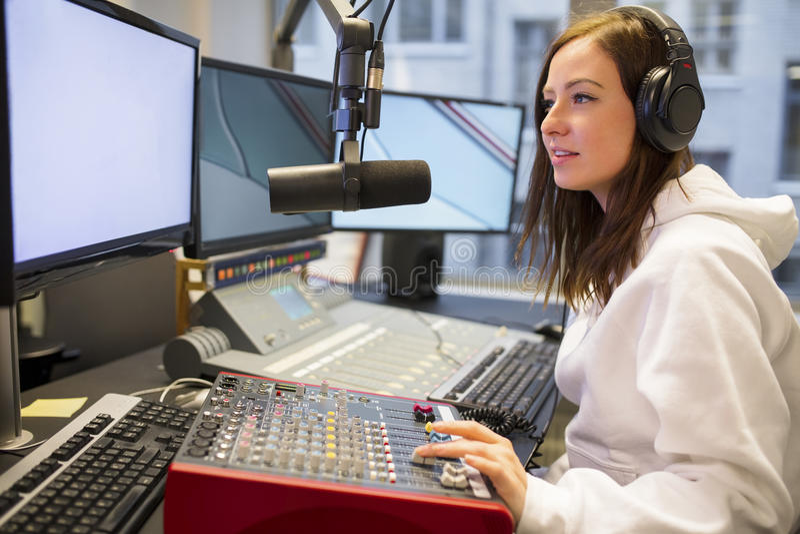 Anfitrión femenino usando el panel de control en la estación de radio foto de archivo libre de regalías