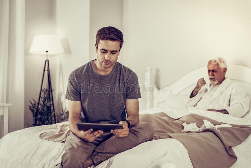 Angången manlig rymmande minnestavla medan hans sjuka hosta för farfar royaltyfri foto