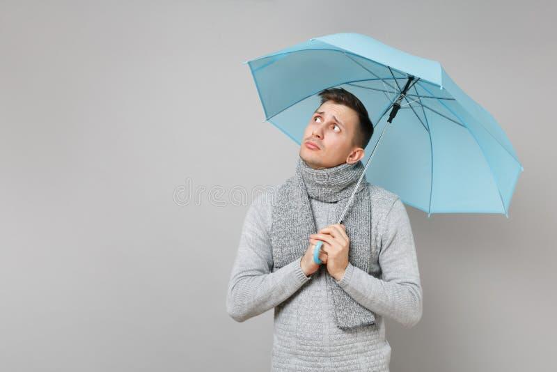 Angången ung man i den gråa tröjan, halsduk som åt sidan ser det hållande blåa paraplyet som isoleras på grå bakgrund Sunt arkivbilder