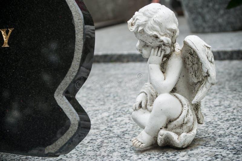 Ange blanc dans le cimetière sur une tombe photo stock