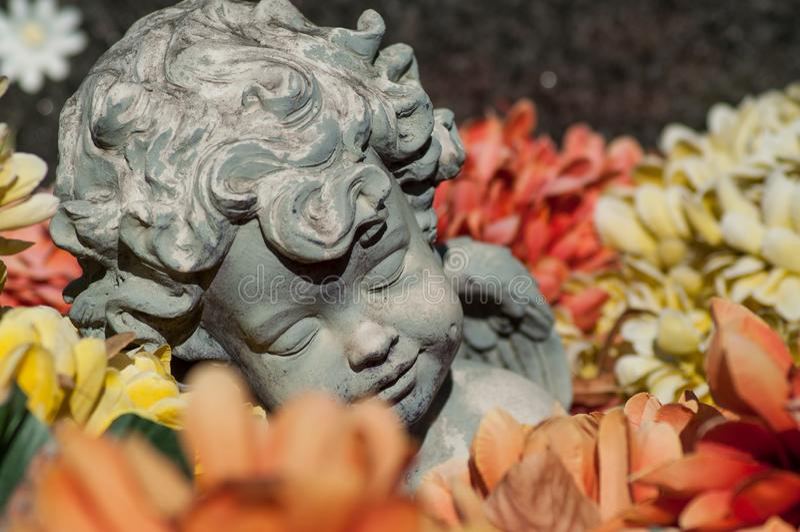 ange lapidé dormant en fleurs colorées sur la tombe à photo stock