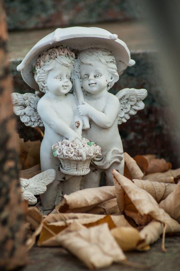 ange lapidé par deux avec le parapluie sur la tombe dans un cimetière photographie stock libre de droits