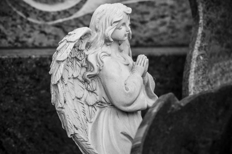 ange lapidé priant sur la tombe au cimetière images stock