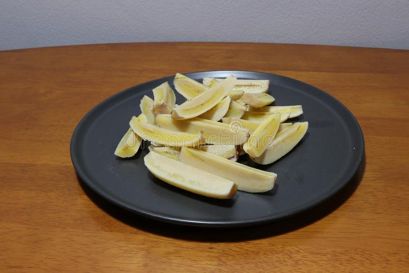 Angebaute Banane kochte und Schnitt in Stücke im schwarzen Teller O stockbilder