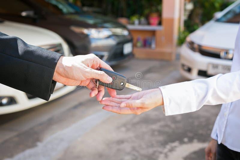 Angebotautoschlüssel des Verkäufers zu Kunden am Ausstellungsraumgebrauchtwagen stockfotografie