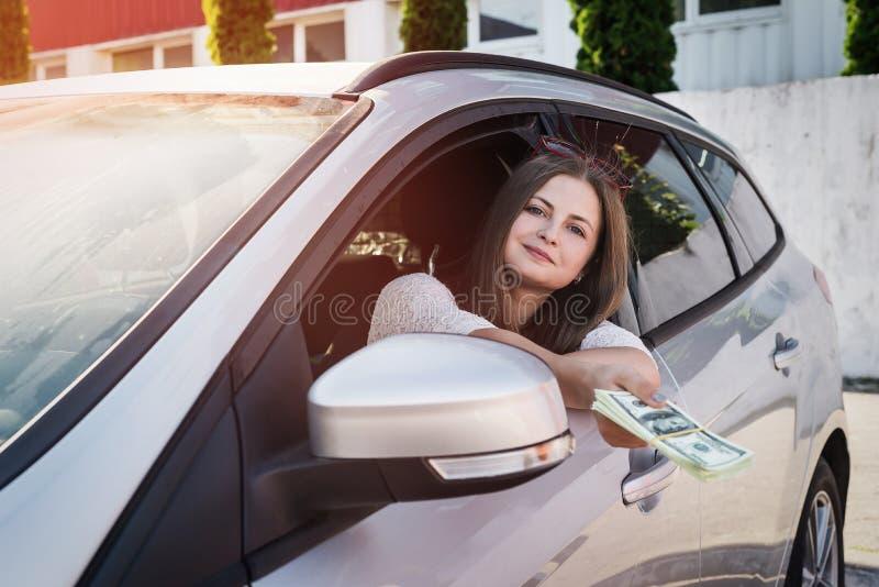 Angebotdollar der glücklichen Frau vom Autofenster lizenzfreies stockbild