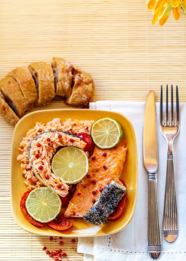 Angefüllt fischen Sie einen Lachs mit Scheiben einer Zitrone oder des Kalkes auf einer Platte stockfotografie