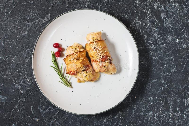 Angefüllte Hühnerbrust eingewickelt im Speck auf einer Platte auf Steintabelle stockfotos