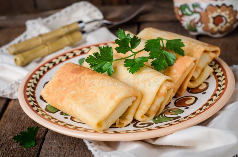 Angefüllte russische Pfannkuchen rollt mit Fleisch in der traditionellen Lehmschüssel auf hölzernem Hintergrund Getontes Bild Sel lizenzfreies stockbild