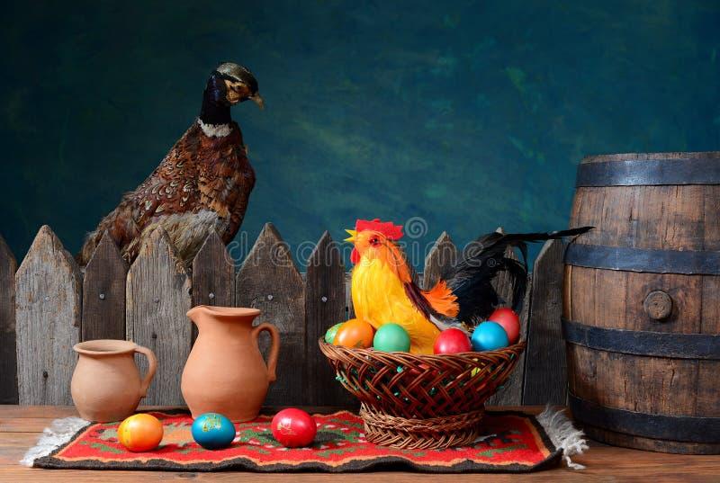 Angefüllter Fasan und Hahn mit farbigen Eiern stockbild