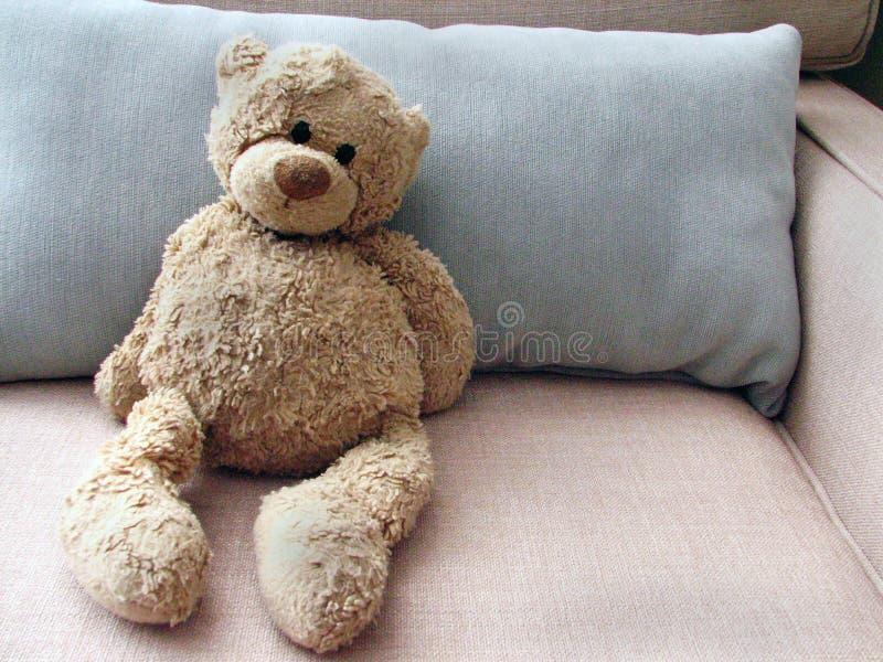 Angefüllter Spielzeug-Teddybär betreffen Couch mit Kissen lizenzfreie stockfotos