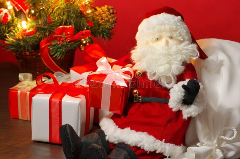 Angefülltes Spielzeug Santa Claus und viele Weihnachtsgeschenke. lizenzfreies stockfoto