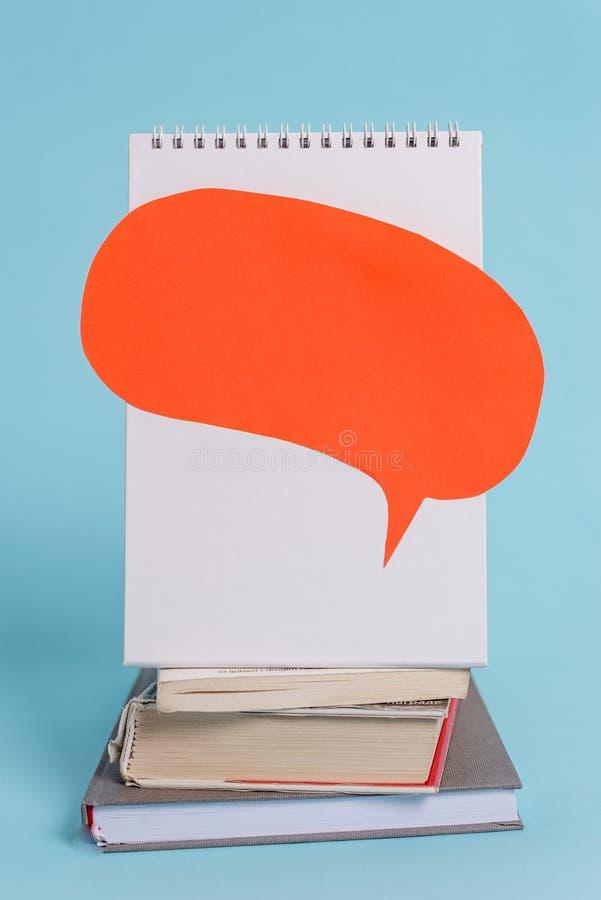 Angehäufte Staplungsbücher, die Spracheblasenliegenden ruhigen kühlen Pastellhintergrund des gewundenen Notizbuches stehen Leere  stockfoto