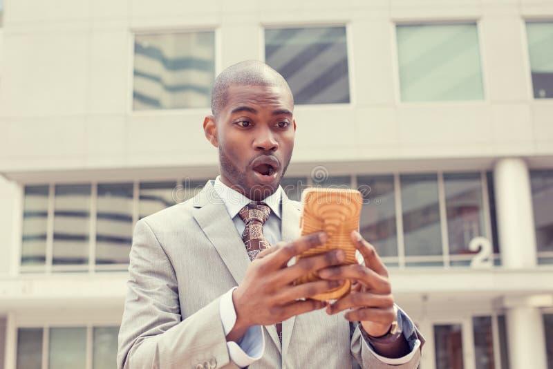 Angelägen affärsman som ser telefonen som ser dåliga nyheter med äckligt chockat framsidauttryck royaltyfria bilder