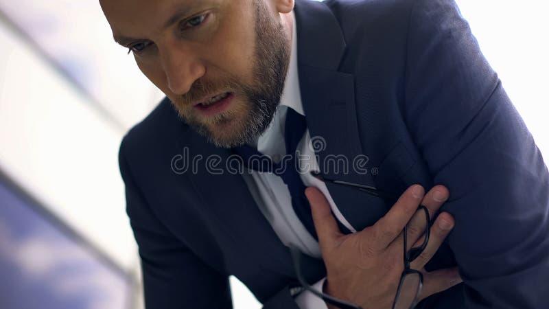 Angelägen bröstkorg för känsla för affärsman att smärta, överansträngd chef, hjärtinfarkt arkivbild