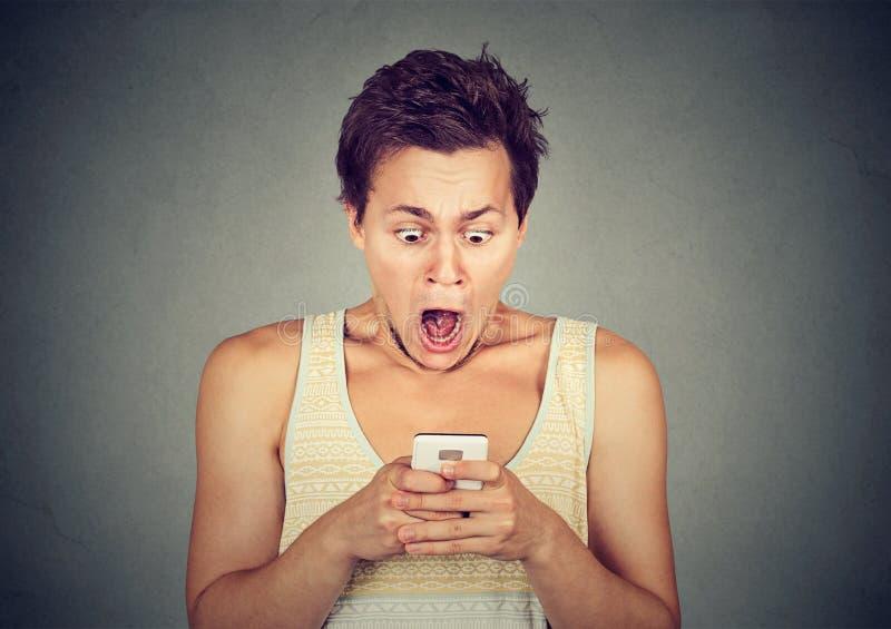 Angelägen chockad man som ser telefonen som ser dåliga nyheterfoto arkivbilder