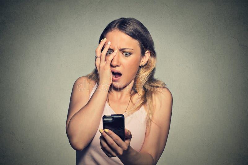 Angelägen förskräckt ung flicka som ser telefonen som ser dåliga nyheter royaltyfri bild