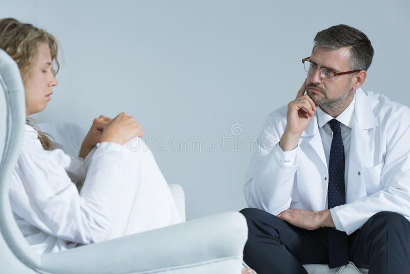 Angelägen kvinna med en psykiater arkivbilder