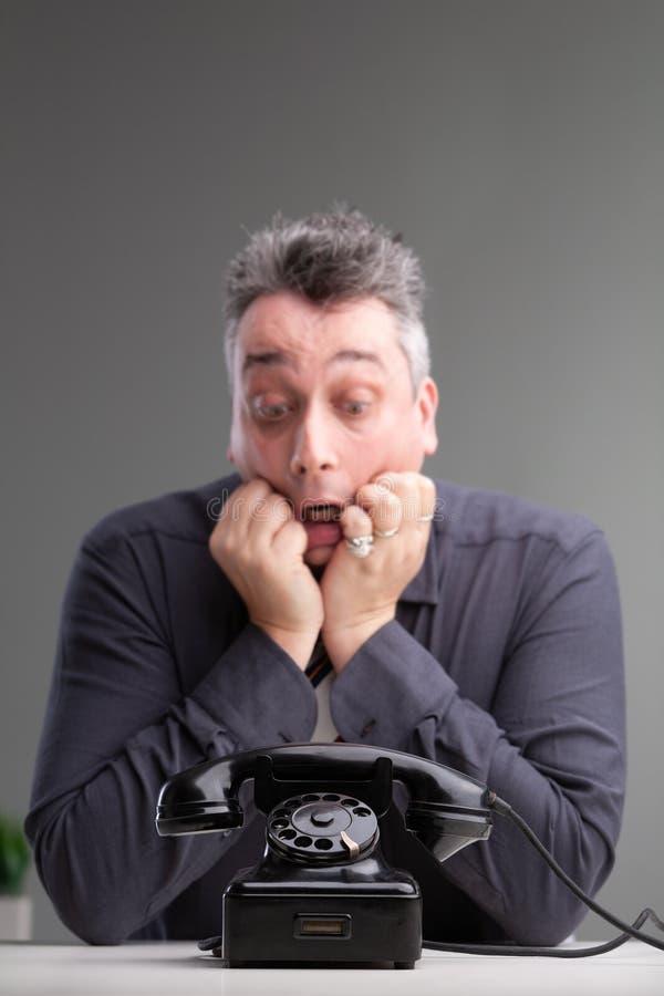 Angelägen man som ser en telefon i oro royaltyfria foton