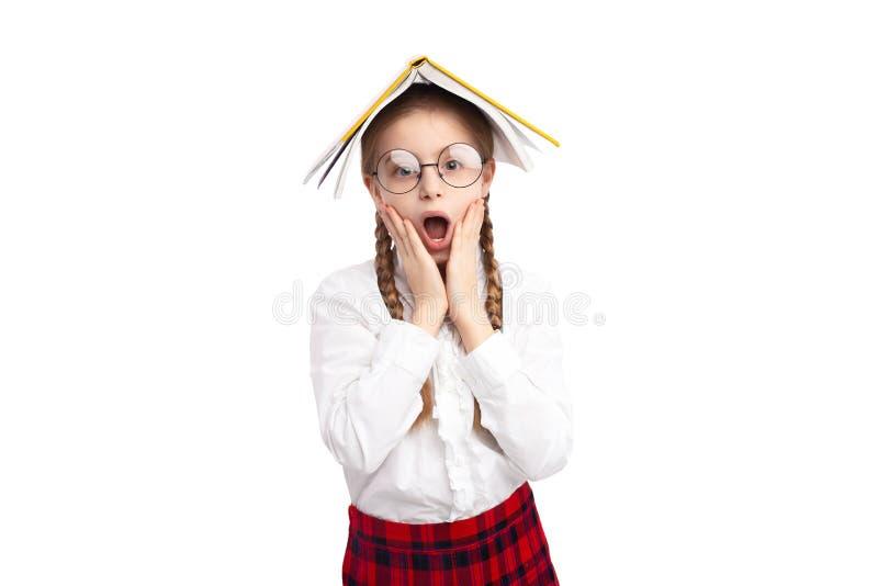 Angelägen nerdy flicka med läroboken på huvudet royaltyfria bilder