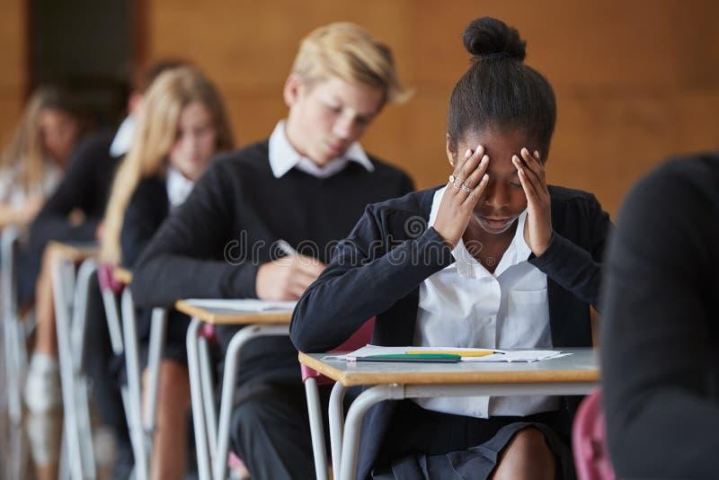 Angelägen tonårs- studentSitting Examination In skola Hall arkivfoton