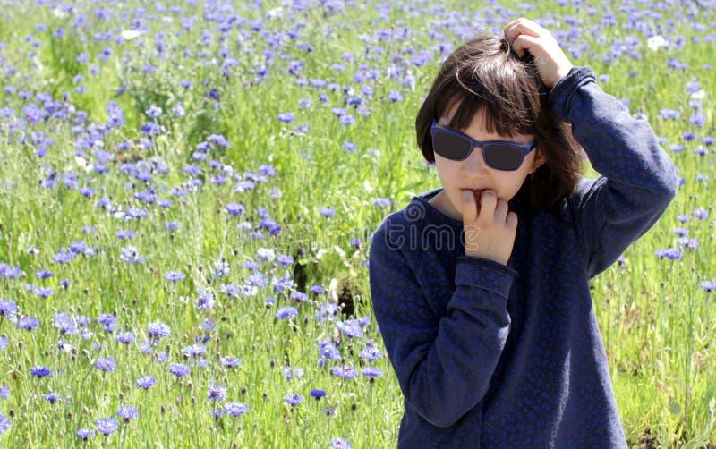 Angeläget barn med solglasögon som har bekymmer över blåklintfältet som är utomhus- royaltyfri foto