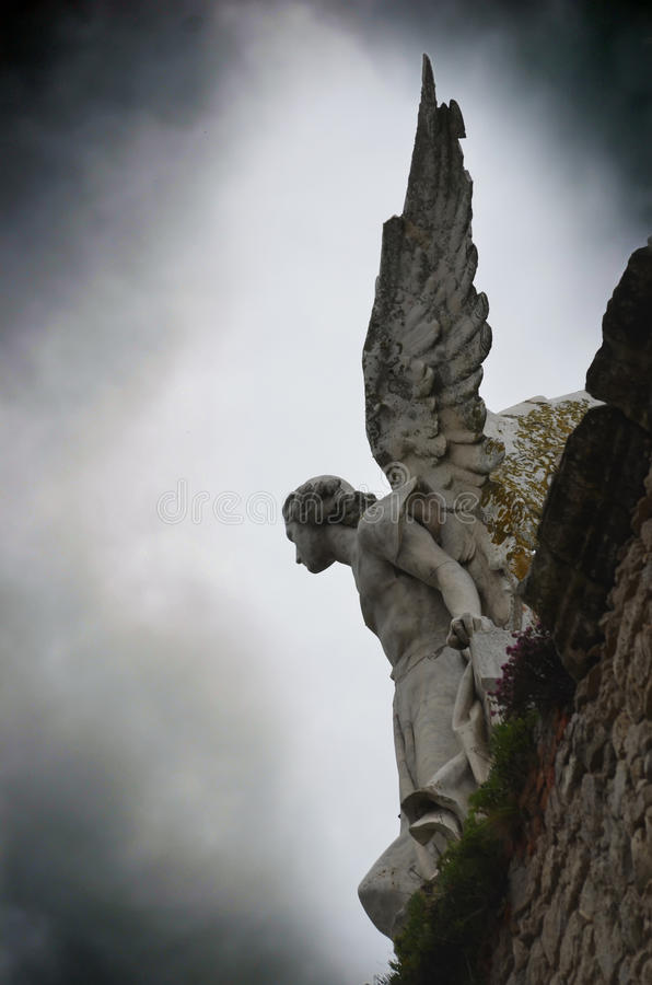 The angel. A sculpture of an angel on the top of a stone wall