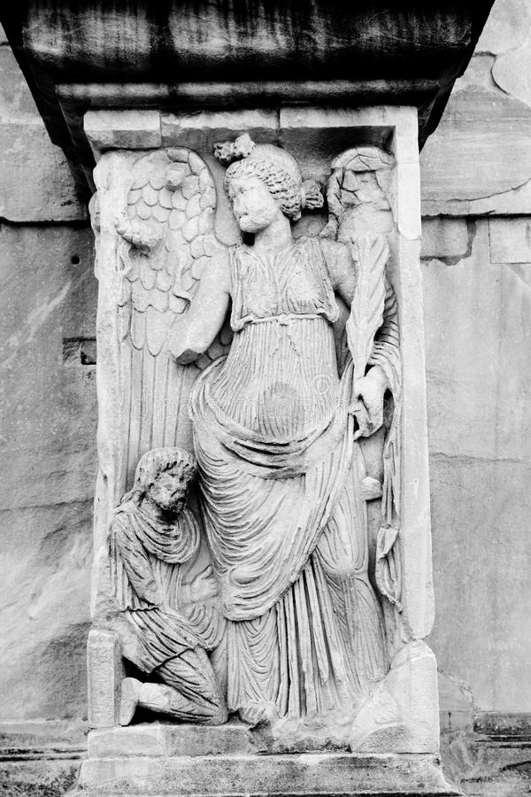 Angel, Arch of Constantine. Angel in the arch of Constantine, near to Coliseum. Century IV. Monochrome photography royalty free stock photo