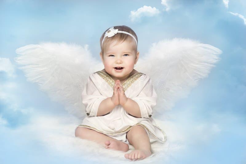 Angel Baby mit Amur-Flügeln, glücklicher Kinderamor, der auf Unschärfe-Himmel sitzt stockbilder