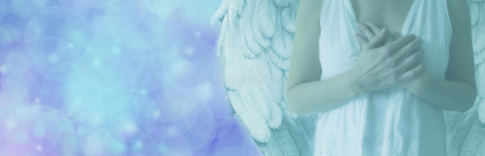 Angel on Blue Bokeh light banner. Cropped Angel showing torso in white robes with hands held over heart on a misty blue bokeh background with copy space on left royalty free illustration