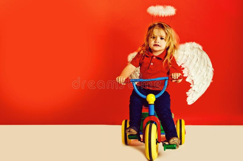 Angel boy for valentine greeting, beautiful cupid on bike. Angel boy on red background for valentine greeting, beautiful cupid on bike with blonde hair and halo royalty free stock image